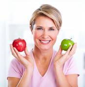 Mature smiling woman with apple. Stock Photos