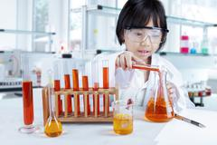 Little girl pouring reagent into flask Stock Photos