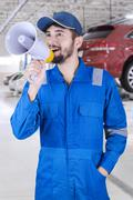 Mechanic announces news in showroom Stock Photos