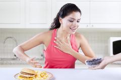 Model chooses healthy blueberry and avoid burger - stock photo
