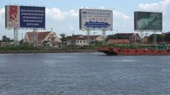Cargo vessel sails past various billboards on Saigon river, Vietnam Stock Footage