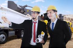 Two engineers observe the construction site - stock photo