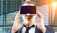 Businessman uses Virtual Reality VR head-mounted display Stock Photos