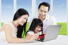 Young parents and their child buy online - stock photo