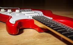 body part of red 6 string guitar - stock photo