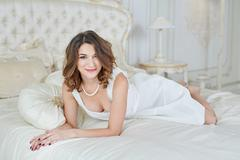 beautiful woman in evening dress with decollete lying on bed - stock photo