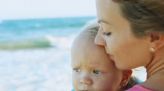 Woman with young son on the beach Stock Footage