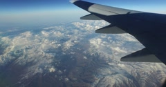 Flying in jet airplane over big mountains left side wing window view Stock Footage