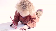 little blond boy laying on the floor and draw on the paper - stock footage