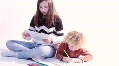 a little blond boy drawing and his sister playing with a tablet - stock footage
