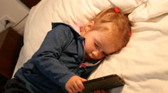 Little sleepy child girl typing game app on smart phone lying on a bed Stock Footage
