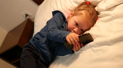 Little sleepy child girl typing game app on smart phone lying on a bed - stock footage
