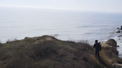 man and dog climbing up to a cliff and looking far in the sea slow motion - stock footage