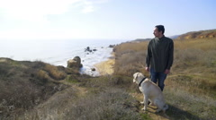 man and dog standing on a hill by the sea slow motion - stock footage