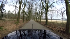 Looking back over roof of black car moving fast over forest road 4k Stock Footage