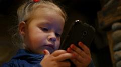 Little kid girl watching cartoons via smart phone display in dark place Stock Footage
