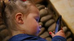 Little kid girl watching cartoons via smart phone display Stock Footage