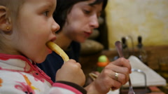 Little child kid girl eating french fries potato with fingers in restaurant Stock Footage