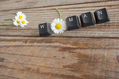 WOMAN wrote with keyboard keys on wooden background - stock photo