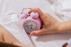 Female hand stopping alarm clock. Stock Photos