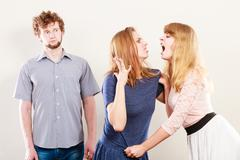 Aggressive mad women fighting over man. - stock photo