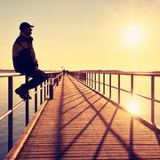 Man in warm jacket and baseball cap sit on pier handrail construction and enj Stock Photos