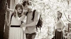 Jealous girl looking at flirting couple outdoor. - stock photo