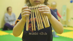 Small child plays a musical instrument ratchet Stock Footage