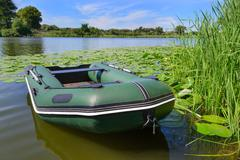 Inflatable boat on the a river near a shore - stock photo