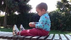 Toddler focussed on peelings a mandarin- Stock Footage