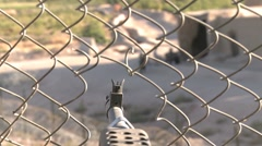 War in Afghanistan - POV Rack focus assault rifle through fence to Afghans Stock Footage