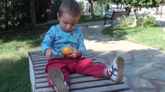 Toddler peels a mandarin sitting on a bench- Stock Footage