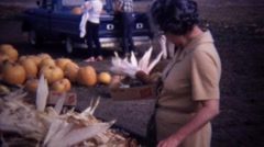 1967: Mature women buying indian colored corn farmstand market. - stock footage
