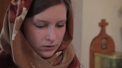 The girl in the Church with a scarf on her head praying Stock Footage
