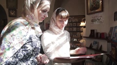 Two girls are in the Church flipping through a large book Stock Footage
