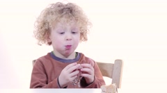 a little blond boy eating a piece of cheese - stock footage
