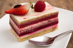 raspberry cake in a plate on wooden table - stock photo