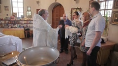 The Holy father into the Church baptized the baby in the tub of Holy water Stock Footage