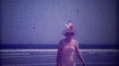 1949: Women wearing tall funny sun hat walking on ocean beach. Stock Footage