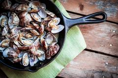 Cast Iron Skillet Of Delicious Fresh Steamer Clams With Garlic And Basil On R Stock Photos