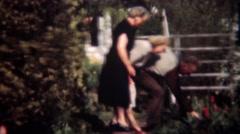 1949: Gentleman flirt picking garden rose for older women. - stock footage