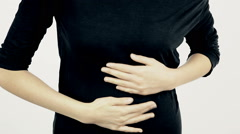 Hands of woman pushing stomach for strong ache and pain Stock Footage