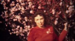 1949: Lady in red posing at pink spring flowering tree blossoms. Stock Footage