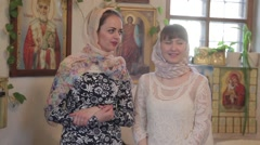 Two young women in headscarves in the Church communicate Stock Footage