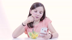 Stock Video Footage of a young teenage girl eats fruit and playing with her phone
