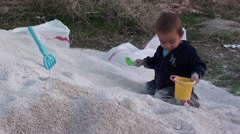 Boy plays with toys on mortar sand pile 2 Stock Footage