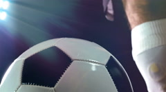 Footballer in boots putting his leg on a ball, black background Stock Footage