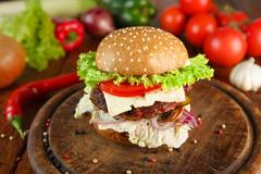 Meet and cheese burger at wooden desk - stock photo
