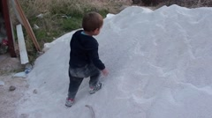 Small boy climbs a mortar sand pile Stock Footage