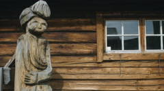 Wooden statue against log wall. Hand held Stock Footage